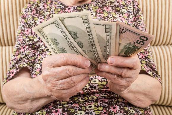 Senior woman holding out money