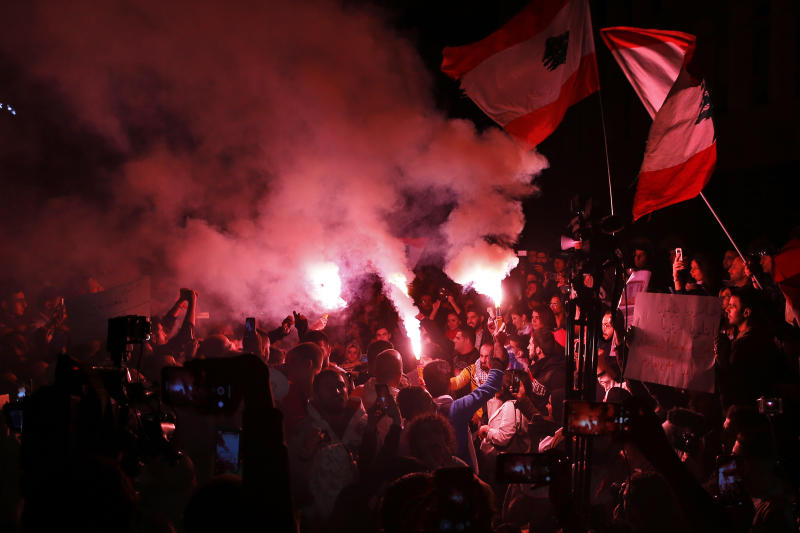 Protesters hold flares and Lebanese flags, during ongoing protests against the Lebanese government, in front of the Central Bank, in Beirut, Lebanon, Thursday, Nov. 28, 2019. Lebanon paid back a Eurobond worth $1.5 billion that was scheduled to mature Thursday, a Finance Ministry official said, pacifying concerns of a first-ever default on its debt amid the worst financial crisis in three decades. (AP Photo/Bilal Hussein)