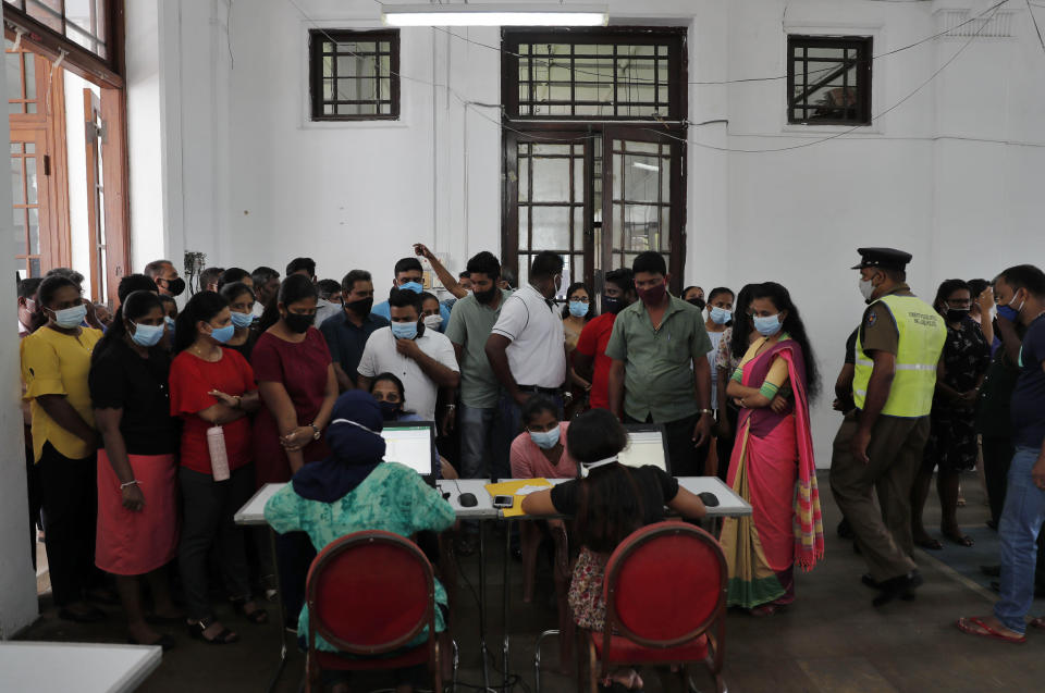 Employees of Colombo municipal council crowd around a table to give their swab samples to test for COVID-19 in Colombo, Sri Lanka, Wednesday, Oct. 7, 2020. Authorities in Sri Lanka on Wednesday widened a curfew and warned of legal action against those evading treatment for COVID-19 after reporting an escalating cluster centered around a garment factory in the capital's suburbs. (AP Photo/Eranga Jayawardena)