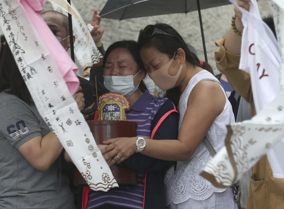 The families of the victims in a train crash try to conjure their spirits near Taroko Gorge in Hualien, Taiwan on Saturday, April 3, 2021. The train partially derailed in eastern Taiwan on Friday after colliding with an unmanned vehicle that had rolled down a hill, killing and injuring dozens. (AP Photo/Chiang Ying-ying)