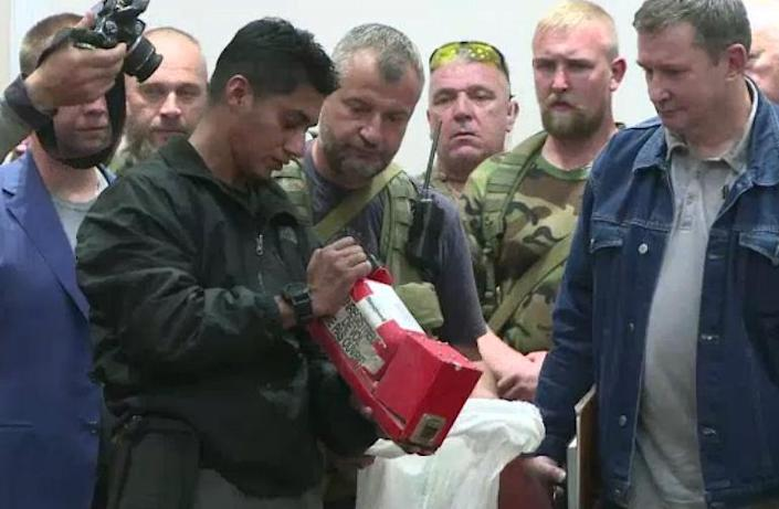 An AFPTV video image shows a Malaysian investigator checking one of two black boxes recovered from the crash site of flight MH17, during a press conference in Donetsk, eastern Ukraine on July 22, 2014 (AFP Photo/Damien Simonart)