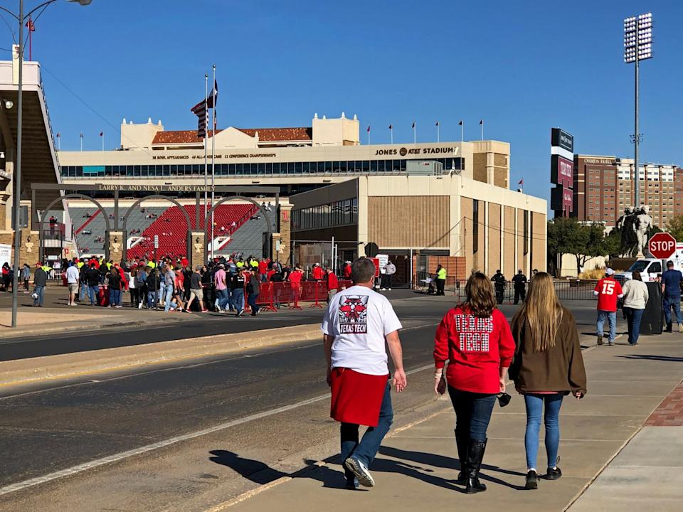 People in red Texas Tech gear walk toward an entrance to the football stadium