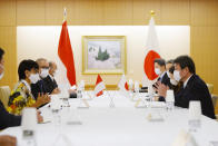 Japan's Foreign Minister Toshimitsu Motegi, right, and Indonesian Foreign Minister Retno Marsudi, left, wearing protective face masks, speak during the Japan Indonesia Foreign Ministers meeting in Tokyo on Monday, March 29, 2021. Indonesian Foreign Minister Retno Marsudi and Defense Minister Prabowo Subianto are in Japan from March 28-30, 2021. (David Mareuil/Pool Photo via AP)