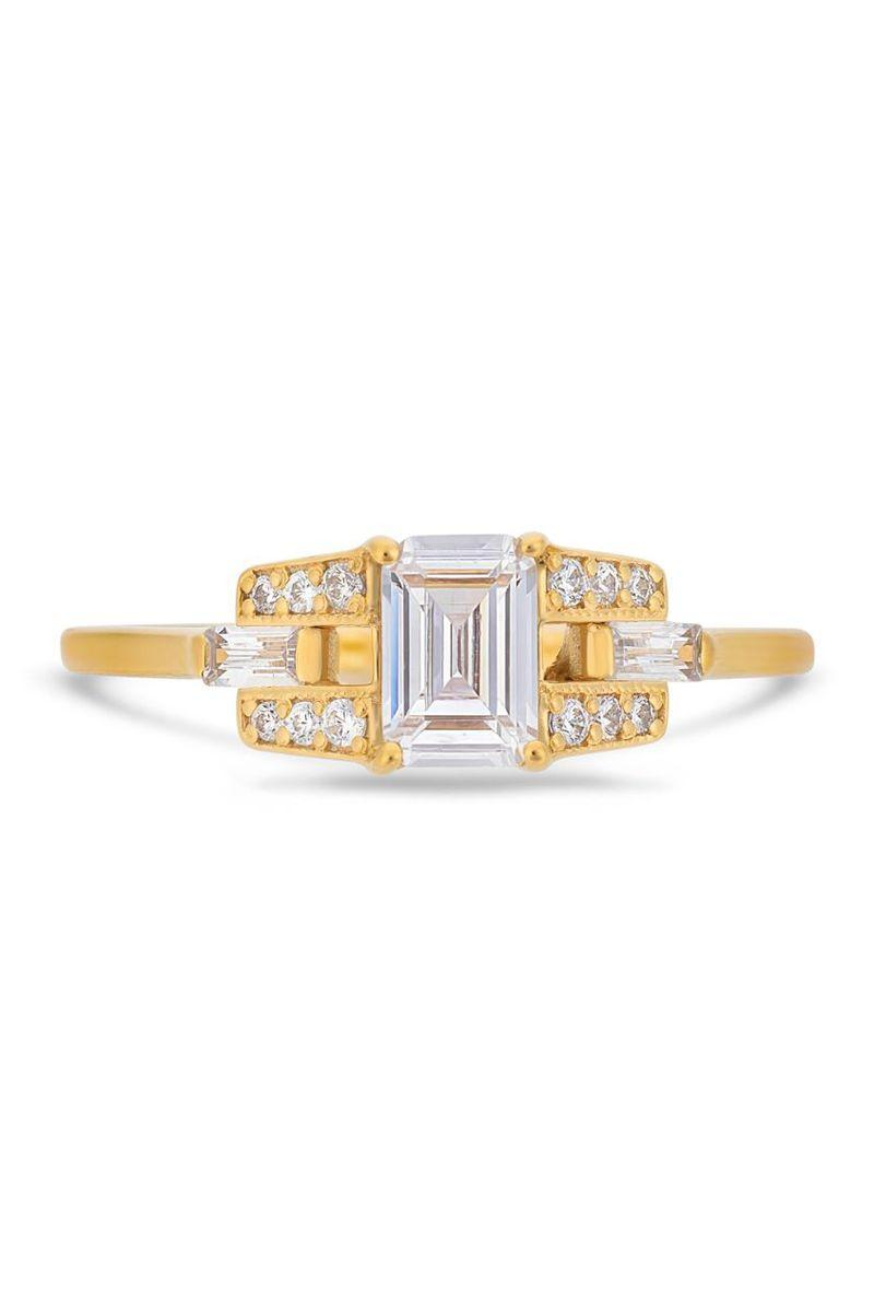 "<p><em><strong>V by Laura Vann</strong> White Emerald Cut Diamond, White Baguette Side Stones and White Brilliant Cut Diamonds</em><em> in 18K yellow gold</em><em>, $7,080,</em><em> <a href=""http://vbylauravann.com/"" rel=""nofollow noopener"" target=""_blank"" data-ylk=""slk:vbylauravann.com."" class=""link rapid-noclick-resp"">vbylauravann.com.</a></em></p><p><a class=""link rapid-noclick-resp"" href=""https://vbylauravann.com/collections/yellow-gold-engagement-rings/products/emerald-cut-diamond-buckle-ring-in-yellow-gold?variant=31199559286818"" rel=""nofollow noopener"" target=""_blank"" data-ylk=""slk:SHOP"">SHOP</a></p>"