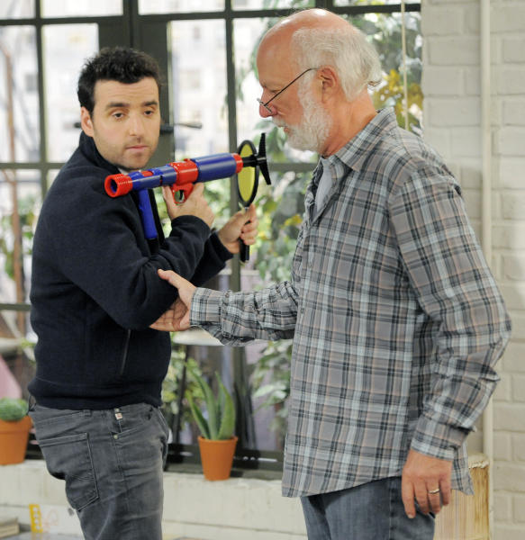 """James Burrows, right, director of the television series """"Partners,"""" directs cast member David Krumholtz on the set on Wednesday, Sept. 19, 2012, at Warner Bros. Studios in Burbank, Calif. Burrows isn't a household name. But behind the scenes Burrows reigns as a comedy giant. He's a director whose brand of funny business has helped shape TV comedy season after season. (Photo by Chris Pizzello/Invision/AP)"""