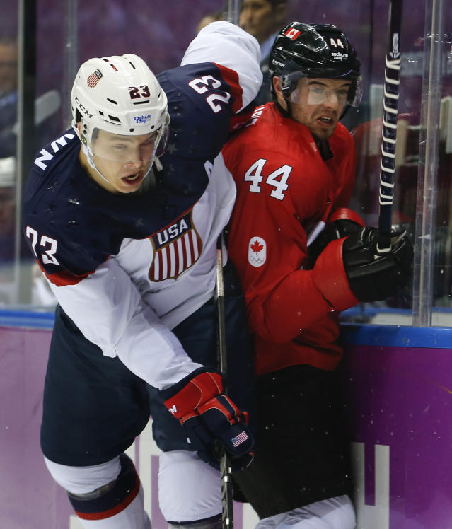 USA forward Dustin Brown, left, and Canada defenseman Marc-Edouard Vlasic crash the boards during the first period of a men's semifinal ice hockey game at the 2014 Winter Olympics, Friday, Feb. 21, 2014, in Sochi, Russia. (AP Photo/Petr David Josek)