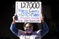 FILE - In this Nov. 2, 2020, file photo, demonstrator Gina Dusterhoft holds up a sign as she walks to join others standing across the street from the federal courthouse in Houston, before a hearing in federal court involving drive-thru ballots cast in Harris County. In 2020, election officials in Harris County, Texas, which includes the Democratic stronghold of Houston and is one of the most racially diverse in the nation, went further than anywhere else in the state to create new ways to vote. (AP Photo/David J. Phillip, File)