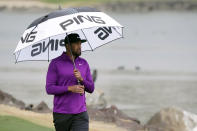Tony Finau carries an umbrella in the rain on the 18th fairway during the third round of The American Express golf tournament on the Pete Dye Stadium Course at PGA West, Saturday, Jan. 23, 2021, in La Quinta, Calif. (AP Photo/Marcio Jose Sanchez)