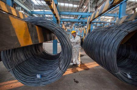 An employee inspects newly-made steel coils at a steel plant in Lianyungang, Jiangsu province October 11, 2014.  REUTERS/China Daily