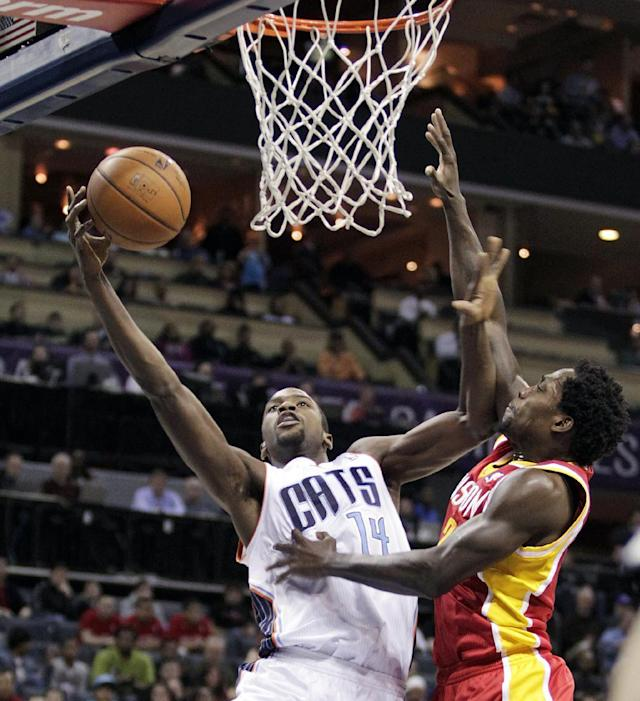 Charlotte Bobcats' Michael Kidd-Gilchrist (14) muscles his shot in against Houston Rockets' Patrick Beverley during the first half of an NBA basketball game in Charlotte, N.C., Monday, March 24, 2014. (AP Photo/Bob Leverone)