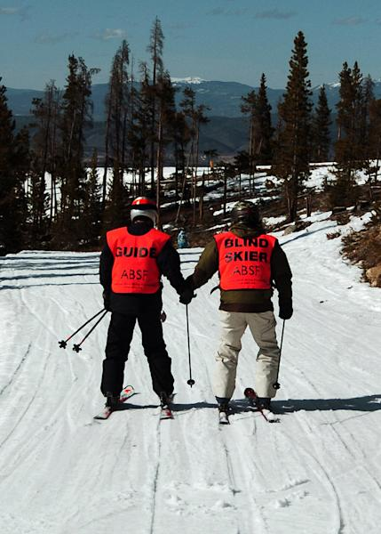 In this photo taken March 29, 2013, blind skier Wally Mozdzierz, right, skis at Colorado's Winter Park resort with his guide, Joe Ferrick. The American Blind Skiing Foundation, a Chicago-based nonprofit, brought Mozdzierz and others to Winter Park and plans another trip to Steamboat Springs this season..(AP Photo/Thomas Peipert)