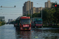 Trucks carrying relief supplies from other parts of China drive along a flooded street in Xinxiang in central China's Henan Province, Monday, July 26, 2021. Forecasters Monday said more heavy rain is expected in central China's flood-ravaged Henan province, where the death toll continues to rise after flash floods last week that killed dozens of people. (AP Photo/Dake Kang)