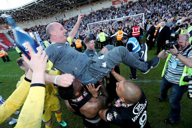 "Soccer Football - League One - Doncaster Rovers vs Wigan Athletic - Keepmoat Stadium, Doncaster, Britain - May 5, 2018 Wigan Athletic manager Paul Cook is lifted by players as they celebrate winning League One Action Images/John Clifton EDITORIAL USE ONLY. No use with unauthorized audio, video, data, fixture lists, club/league logos or ""live"" services. Online in-match use limited to 75 images, no video emulation. No use in betting, games or single club/league/player publications. Please contact your account representative for further details."