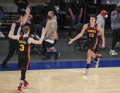 Atlanta Hawks guard Bogdan Bogdanovic (13) celebrates with guard Kevin Huerter (3) after making a 3-point basket against the New York Knicks to tie the score during the fourth quarter of an NBA basketball game Wednesday, April 21, 2021, in New York. (Wendell Cruz/Pool Photo via AP)