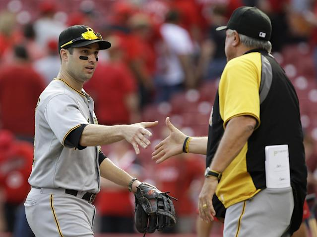 Pittsburgh Pirates second baseman Neil Walker, left, is congratulated by manager Clint Hurdle after they defeated the Cincinnati Reds 8-3 in a baseball game on Saturday, Sept. 28, 2013, in Cincinnati. Walker hit two home runs in the game. (AP Photo/Al Behrman)