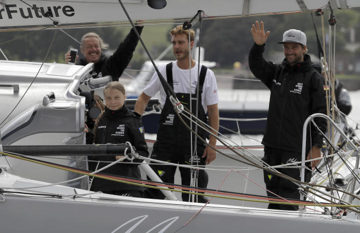Climate change activist Greta Thunberg and the crew wave from Malizia II boat as they depart in Plymouth, England, Wednesday, Aug. 14, 2019. The 16-year-old climate change activist who has inspired student protests around the world will leave Plymouth, England, bound for New York in a high-tech but low-comfort sailboat.(AP Photo/Kirsty Wigglesworth, pool)