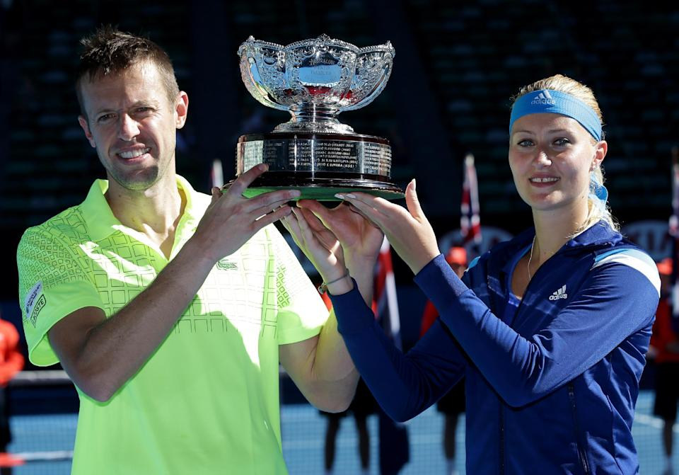 Kristina Mladenovic of France and Daniel Nestor of Canada hold the trophy after defeating Sania Mirza of India and Horia Tecau of Romania in their mixed doubles final at the Australian Open tennis championship in Melbourne, Australia, Sunday, Jan. 26, 2014.(AP Photo/Aaron Favila)