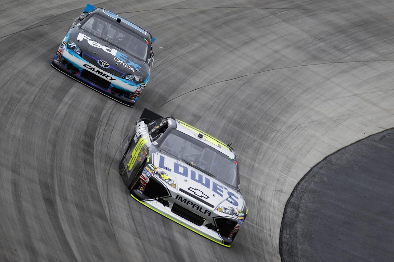 DOVER, DE - OCTOBER 02:  Jimmie Johnson, driver of the #48 Lowe's/Kobalt Tools Chevrolet, leads Denny Hamlin, driver of the #11 FedEx Office Toyota, during the NASCAR Sprint Cup Series AAA 400 at Dover International Speedway on October 2, 2011 in Dover, Delaware.  (Photo by Chris Graythen/Getty Images)