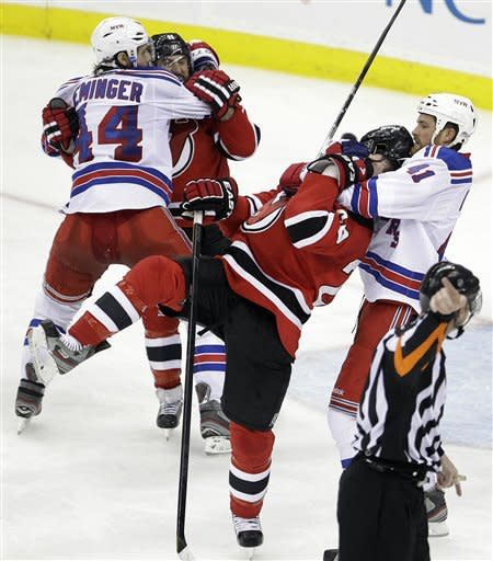 New York Rangers' Stu Bickel, right, grabs at New Jersey Devils' Ryan Carter, center, as Rangers' Steve Eminger, left, grabs Stephen Gionta during a scuffle in the third period of Game 4 of an NHL hockey Stanley Cup Eastern Conference final playoff series, Monday, May 21, 2012, in Newark, N.J. The Devils won 4-1. (AP Photo/Julio Cortez)