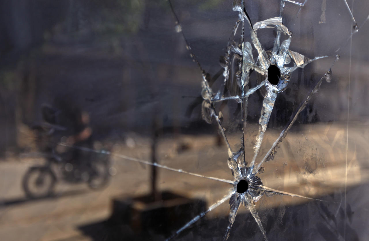 FILE - In a Tuesday, June 5, 2012 file photo, a Syrian man on a motorcycle is seen reflected in the glass door of a shop which has bullet holes, in the town of Taftanaz, 15 kilometers east of Idlib, Syria. At dawn on April 3, Syrian forces shelled the town in the first volley of what residents say was a massive assault after a string of large protests calling for the end of the autocratic rule of President Bashar Assad. (AP Photo)