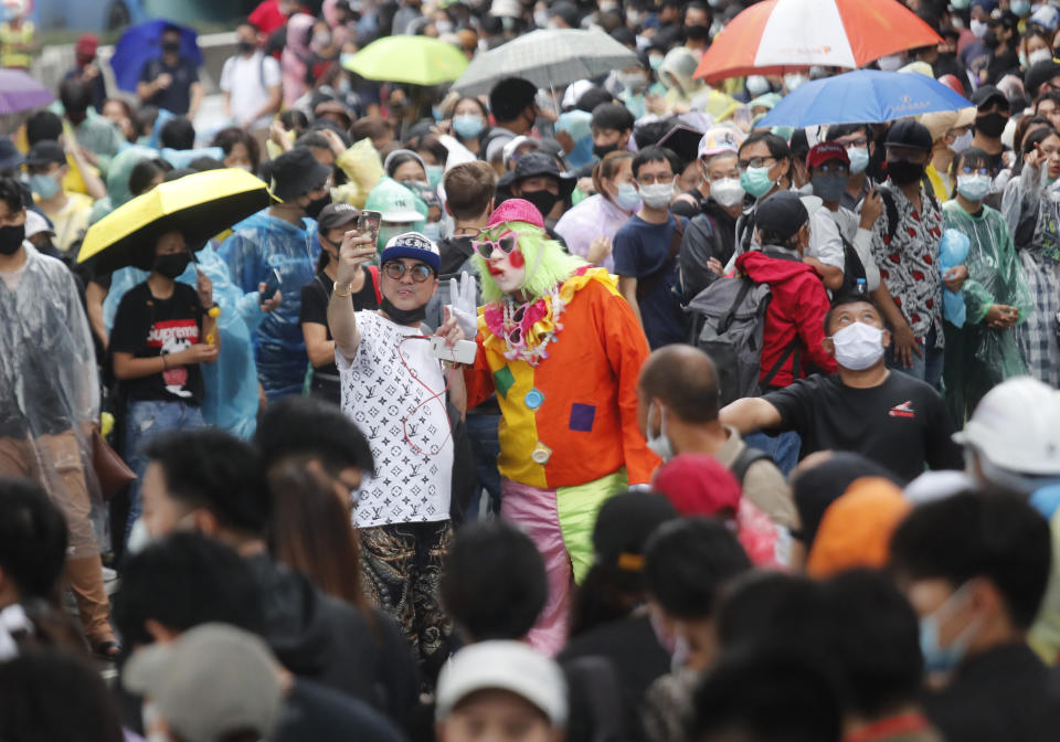 A pro-democracy protester takes a selfie with a clown as they gather during a protest near a main train station in Bangkok, Thailand, Saturday, Oct. 17, 2020. The authorities in Bangkok shut down mass transit systems and set up roadblocks Saturday as Thailand's capital braced for a fourth straight day of determined anti-government protests. (AP Photo/Sakchai Lalit)