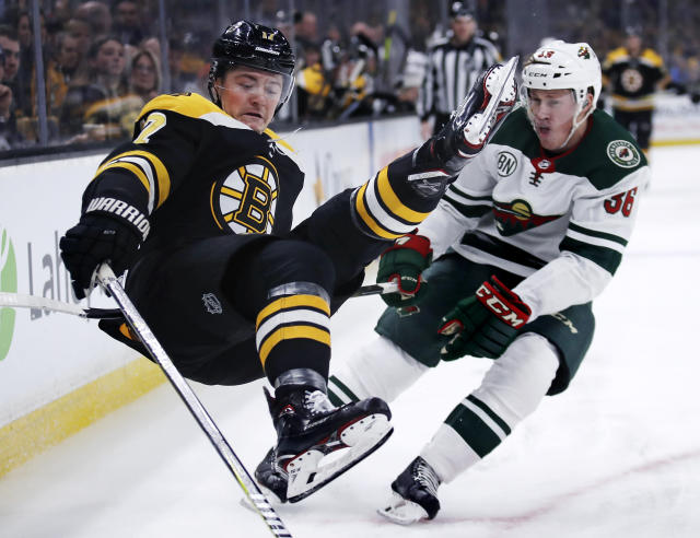 Boston Bruins center Ryan Donato, left, goes airborne after being hit by Minnesota Wild defenseman Nick Seeler during the second period of an NHL hockey game in Boston, Tuesday, Jan. 8, 2019. (AP Photo/Charles Krupa)