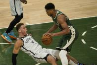 Brooklyn Nets' Blake Griffin draws a charge on Milwaukee Bucks' Giannis Antetokounmpo during the second half of an NBA basketball game Sunday, May 2, 2021, in Milwaukee. (AP Photo/Morry Gash)