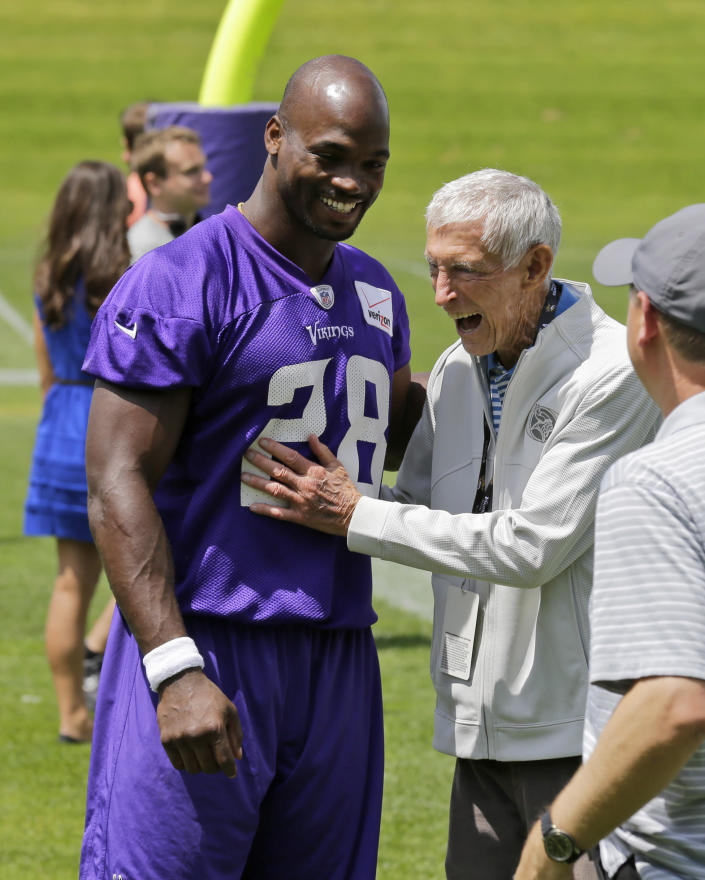 FILE - In this June 18, 2015, file photo, Minnesota Vikings running back Adrian Peterson, left, laughs with former Vikings coach Jerry Burns, right, during NFL football minicamp in Eden Prairie, Minn. Burns, the colorful character who took over as the Vikings' head coach in a time of turmoil and led the team to three playoff berths, has died. He was 94. The team announced Burns' death. Vikings spokesman Bob Hagan said Burns' son-in-law informed him of Burns' death Wednesday morning, May 12, 2021. (AP Photo/Ann Heisenfelt, File)