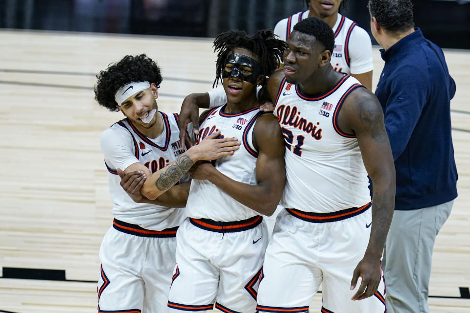 Illinois' Andre Curbelo, left, Ayo Dosunmu, center and Kofi Cockburn (21) hug as they leave the court following an 82-71 win over Iowa in an NCAA college basketball game at the Big Ten Conference tournament in Indianapolis, Saturday, March 13, 2021. (AP Photo/Michael Conroy)
