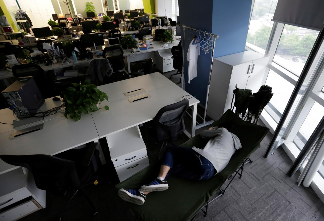 Kou Meng, product manager of RenRen Credit Management Co. in Beijing, sleeps on a camp bed at the office early in the morning on April 27, 2016. (Jason Lee/Reuters)