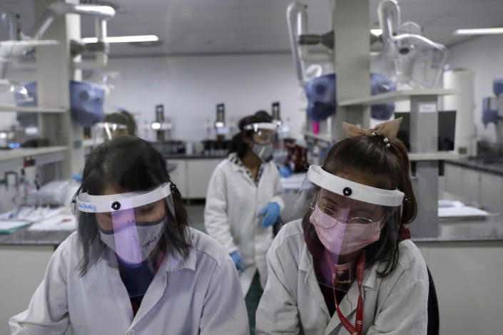 Laboratory employees work on the pilot production phase of Russia's Sputnik V vaccine for COVID-19 at the pharmaceutical company Uniao Quimica in Brasilia, Brazil, Monday, Jan. 25, 2021. (AP Photo/Eraldo Peres)