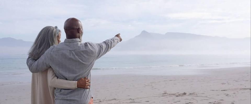 Rear view of happy senior African-American couple standing next to each other while looking at the sea and mountains on beach on beautiful cloudy day.