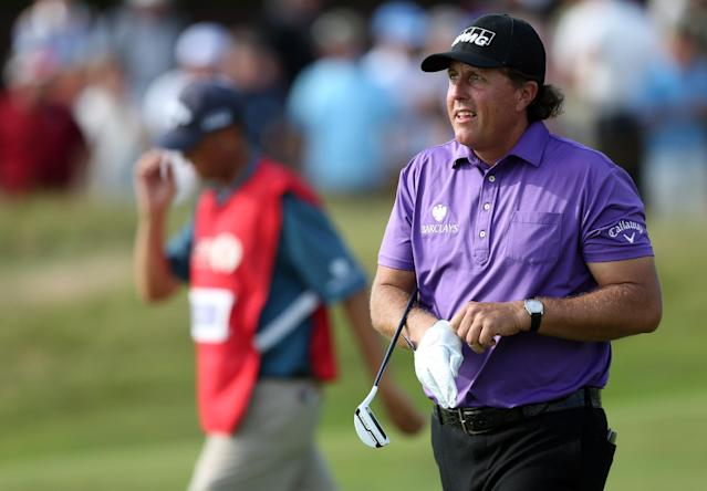 Phil Mickelson of the US puts on a glove to putt on the 15th green during the first day of the British Open Golf championship at the Royal Liverpool golf club, Hoylake, England, Thursday July 17, 2014. (AP Photo/Scott Heppell)