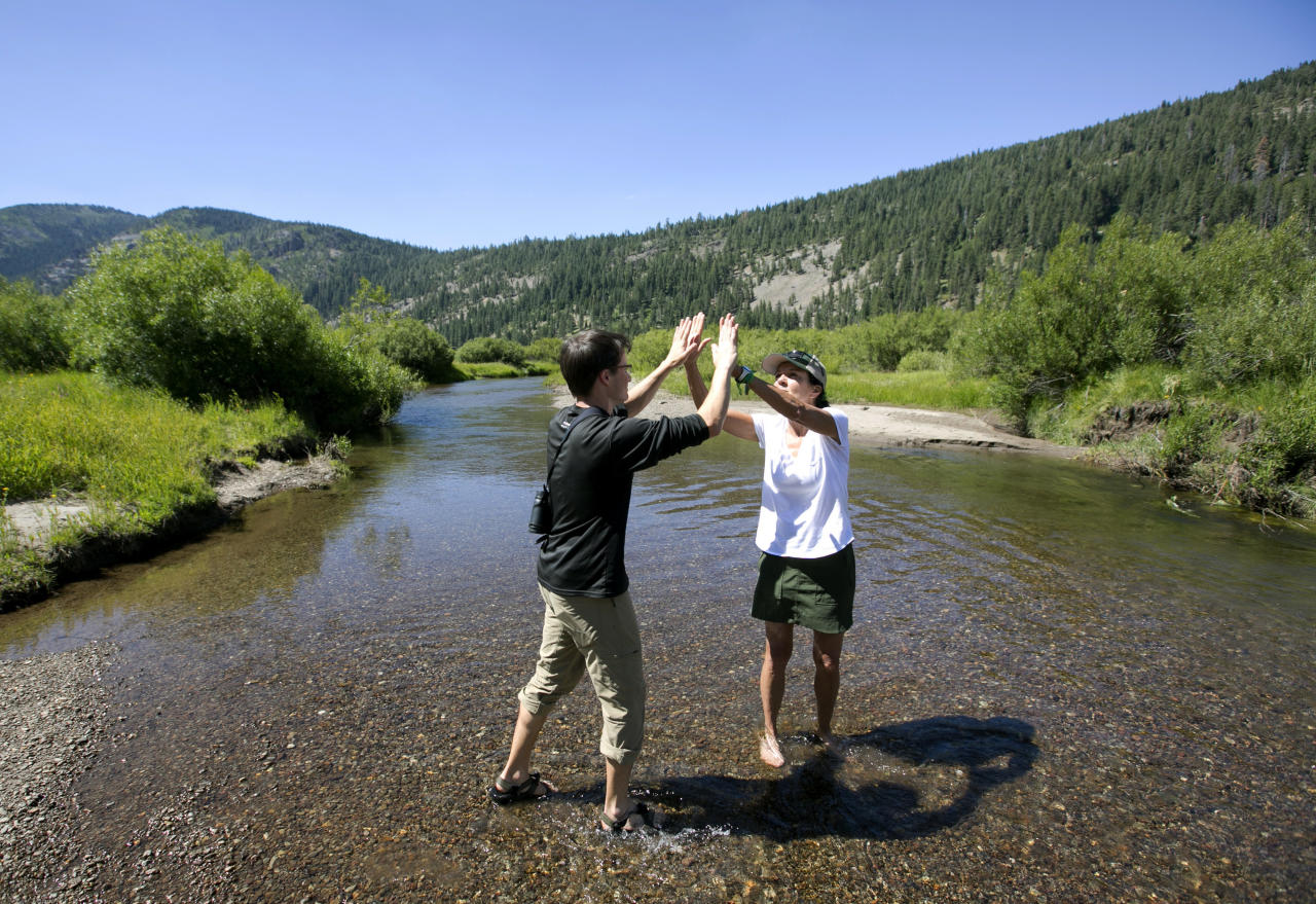 In this photo taken Tuesday, July 25, 2017, standing in the North Fork of Prosser Creek, Elliott Wright, left, of The Nature Conservancy and Kathy Englar, of the Truckee Donner Land Trust, celebrate the recent acquisition of property in the Lower Carpenter Valley near Truckee, Calif. Recently purchased by the Truckee Donner Land Trust, The Nature Conservancy and others, this meadow, hidden from public view for more than a century, is opening for tours. (AP Photo/Rich Pedroncelli)