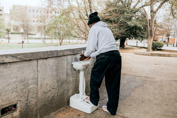 PHOTO: A man who's currently experiencing homelessness washes his hands. (Dani Andujo)