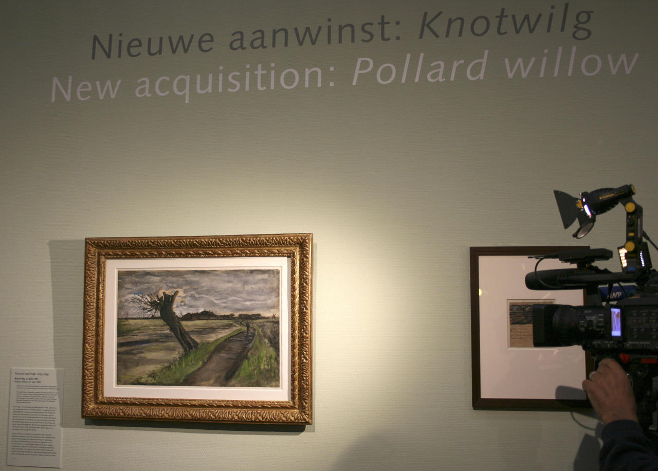 A cameraman films an 1882 water color of a pollard willow by Vincent van Gogh at the Van Gogh Museum in Amsterdam, Netherlands, Thursday May 10, 2012. The Van Gogh Museum unveiled the painting Thursday, the first addition in five years to its world-famous collection of works by the post-impressionist. (AP Photo/Mike Corder)