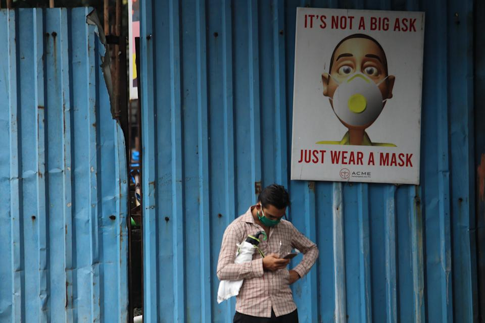 A man uses a mobile phone in front of an Its Not A Big Ask, Just Wear A Mask banner in Mumbai, India on August 12, 2020. India is the third worst-hit nation by the Coronavirus (COVID-19) pandemic after the United States and Brazil. (Photo by Himanshu Bhatt/NurPhoto via Getty Images)