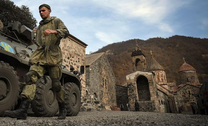 A Russian peacekeeper walks past an armored personnel carrier parked in front of the towers of Dadivank monastery.
