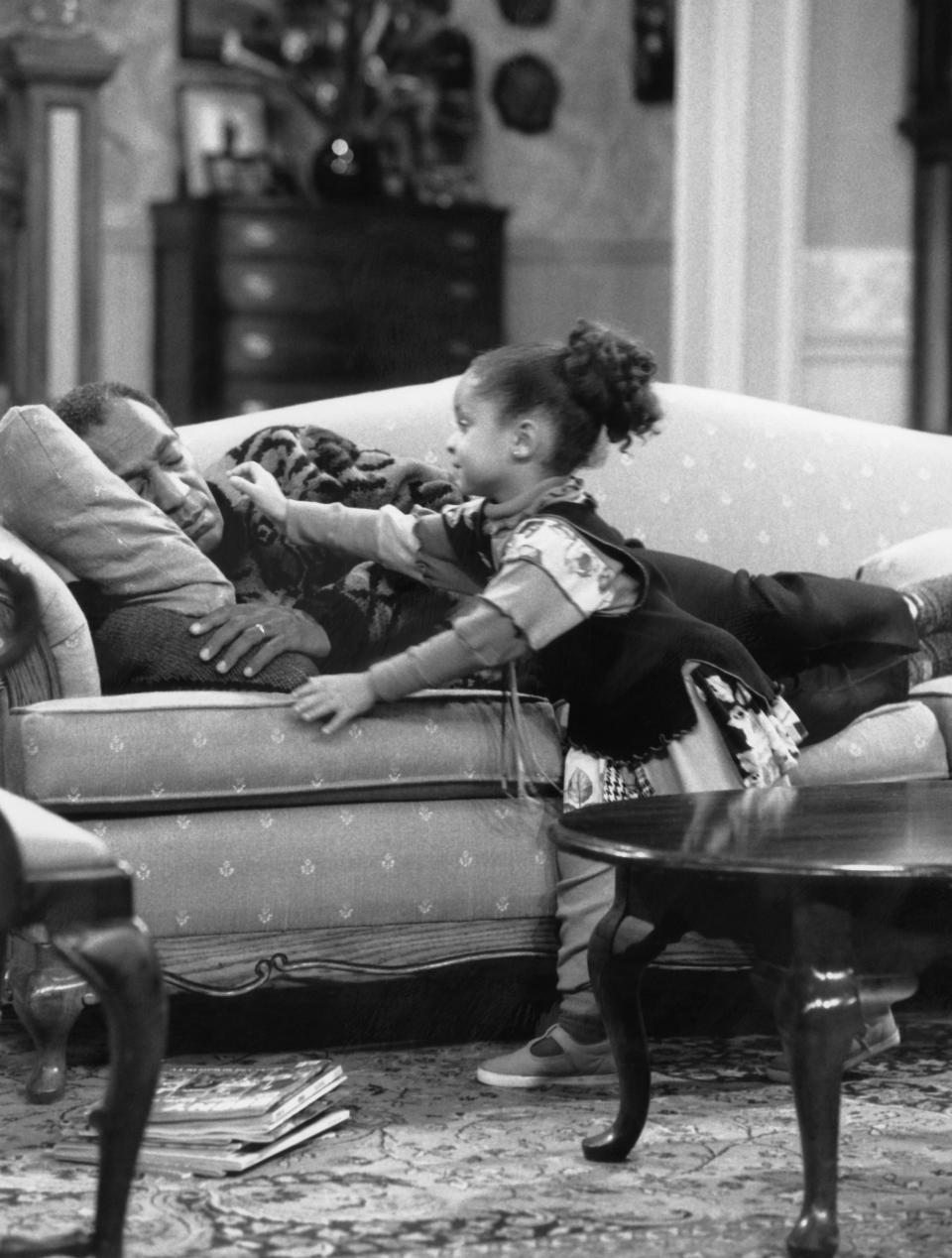 """THE COSBY SHOW -- """"Denise Kendall: Navy Wife"""" Episode 4 -- Air Date 10/12/1989 -- Pictured: (l-r) Bill Cosby as Dr. Heathcliff 'Cliff' Huxtable, Raven-SymonT as Olivia Kendall  (Photo by NBCU Photo Bank/NBCUniversal via Getty Images via Getty Images)"""