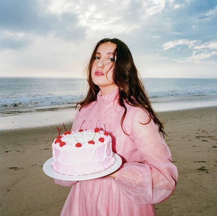 Photo of singer Caity Krone in a pink dress, holding a cake at the beach