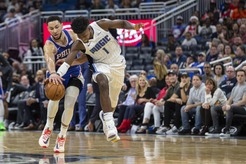 Philadelphia 76ers guard Ben Simmons (25) and Orlando Magic forward Jonathan Isaac (1) fight for the ball during the second half of an NBA basketball game in Orlando, Fla., Friday, Dec. 27, 2019. (AP Photo/Willie J. Allen Jr.)