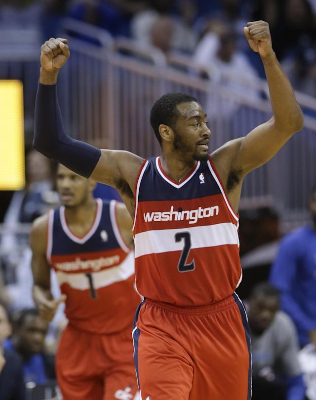 Washington Wizards' John Wall raises his arm as he runs down the court after teammate Trevor Ariza (1) made a 3-point shot against the Orlando Magic during the second half of an NBA basketball game in Orlando, Fla., Friday, March 14, 2014. Washington won in overtime, 105-101. (AP Photo/John Raoux)