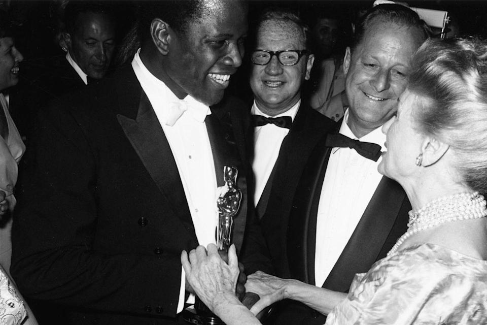 "<p>Attendees at the Governors Ball (the official after-party) congratulated Sidney Poitier on his history-making Best Actor win for <em><a href=""https://www.amazon.com/dp/B000IZ8V9O?ref=sr_1_1_acs_kn_imdb_pa_dp&qid=1547579130&sr=1-1-acs&autoplay=0&tag=syn-yahoo-20&ascsubtag=%5Bartid%7C10055.g.5132%5Bsrc%7Cyahoo-us"" rel=""nofollow noopener"" target=""_blank"" data-ylk=""slk:Lilies of the Field"" class=""link rapid-noclick-resp"">Lilies of the Field</a></em>. He was the first black actor to win that award.</p>"