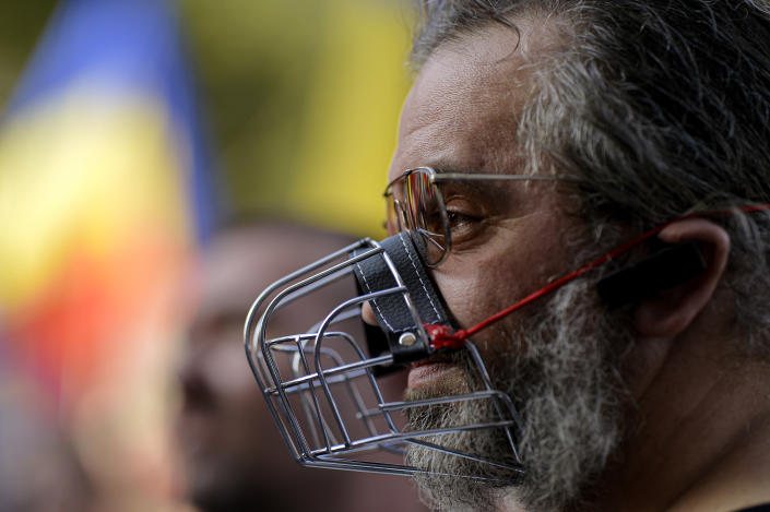 In this photo taken on Saturday, Sept. 19, 2020 a man wears a muzzle during a protest against the COVID-19 pandemic restrictions in Bucharest, Romania. Across the Balkans and the rest of the nations in the southeastern corner of Europe, a vaccination campaign against the coronavirus is overshadowed by heated political debates or conspiracy theories that threaten to thwart the process. In countries like the Czech Republic, Serbia, Bosnia, Romania and Bulgaria, skeptics have ranged from former presidents to top athletes and doctors. Nations that once routinely went through mass inoculations under Communist leaders are deeply split over whether to take the vaccines at all. (AP Photo/Andreea Alexandru)