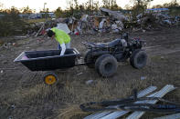Ricky Trahan uses a four wheeler to move and sort debris on their property, after their home was destroyed by both Hurricane Laura and Hurricane Delta in Lake Charles, La., Friday, Dec. 4, 2020. The family is living in tents, with their son, his fiancee and their one year old son living in a camper. His sister's family's home is now gutted and they are living in a camper on the same property. (AP Photo/Gerald Herbert)