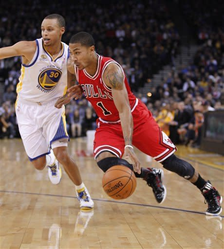 Chicago Bulls' Derrick Rose (1) drives to the basket past Golden State Warriors' Stephen Curry (30) during the first half of an NBA basketball game Monday, Dec. 26, 2011, in Oakland, Calif. (AP Photo/Tony Avelar)