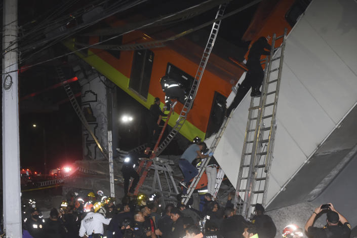 Mexico City fire fighters and rescue personnel work to recover victims from a subway accident after a section of Line 12 of the subway collapsed in Mexico City, Monday, May 3, 2021. The section passing over a road in southern Mexico City collapsed Monday night, dropping a subway train, trapping cars and causing at least 50 injuries and several dead, authorities said. (AP Photo/Jose Ruiz)