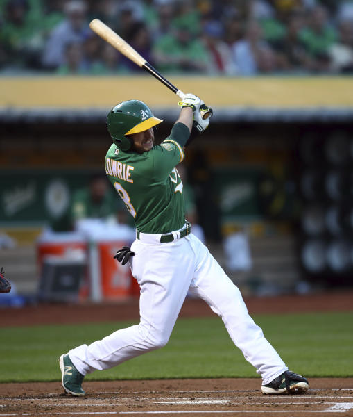 Oakland Athletics' Jed Lowrie follows through on an RBI double off Boston Red Sox pitcher Drew Pomeranz during the first inning of a baseball game Friday, April 20, 2018, in Oakland, Calif. (AP Photo/Ben Margot)