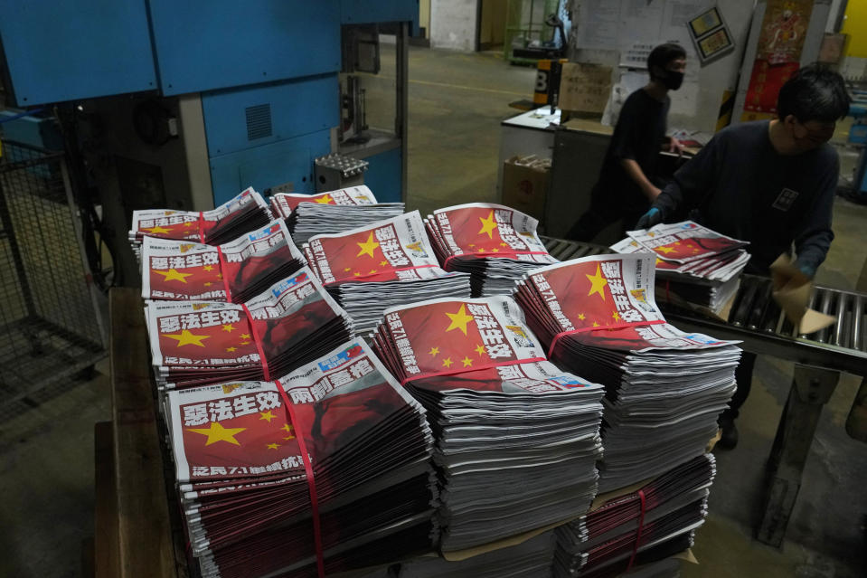 """A worker packs copies of Apple Daily's July 1, 2020, edition seen with its front page title of """"Draconian law is effective, one country two system is dead"""" at the newspaper's printing house in Hong Kong Wednesday, July 1, 2020. A newspaper that has advocated for greater democracy in Hong Kong came under further pressure Thursday, June 17, 2021, with the arrests of three top editors and two senior executives.(AP Photo/Vincent Yu, File)"""