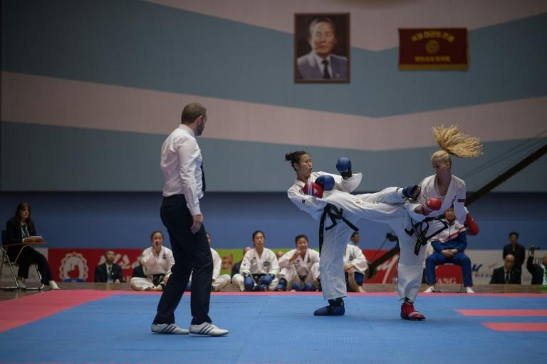 In a photo taken on September 21, 2017 team members from North Korea (C) and Russia (R) fight during the womens team event of 20th ITF World Taewondo Championships in Pyongyang
